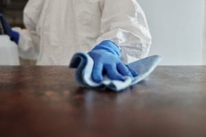 person in white cleaning suite, blue gloves and cleaning